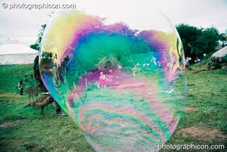 Iridescent reflections in a giant bubble at Big Green Gathering 2003. Cheddar, Great Britain. © 2003 Photographicon