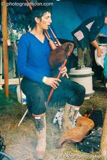 Woman plays a bagbipe by the fireside at Big Green Gathering 2003. Cheddar, Great Britain. © 2003 Photographicon