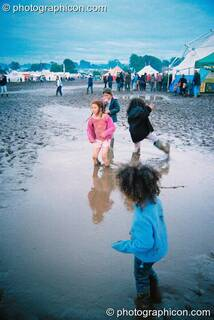 Kids wading through a mud lake at Big Green Gathering 2003. Cheddar, Great Britain. © 2003 Photographicon