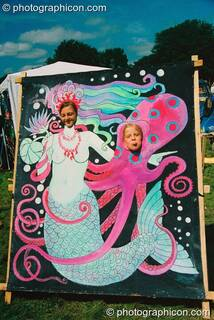 Two girls poke their heads through a mermaid painted board at Big Green Gathering 2003. Cheddar, Great Britain. © 2003 Photographicon