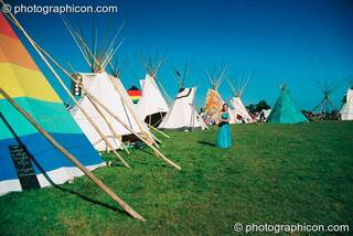 Woman standing in the tipi circle surrounded by a cloudless blue sky at Big Green Gathering 2003. Cheddar, Great Britain. © 2003 Photographicon
