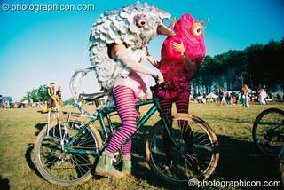 People in fish costumes riding bikes at Big Green Gathering 2003. Cheddar, Great Britain. © 2003 Photographicon