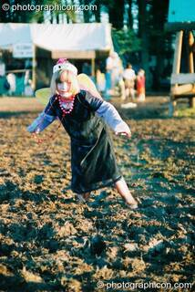 Girl in angel wings and Wellington boots caught in the mud at Big Green Gathering 2003. Cheddar, Great Britain. © 2003 Photographicon