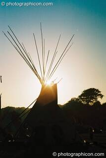 The setting sun framed by tipi poles at Big Green Gathering 2003. Cheddar, Great Britain. © 2003 Photographicon
