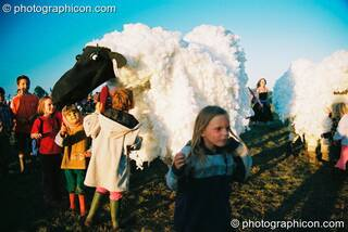 A group of kids flock around a pantomime sheep at Big Green Gathering 2003. Cheddar, Great Britain. © 2003 Photographicon