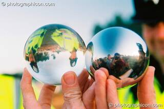 Two policeman are seen inverted through a clear plastic juggling ball, while the photographer is seen reflected in an adjacent steel juggling ball at Big Green Gathering 2003. Cheddar, Great Britain. © 2003 Photographicon