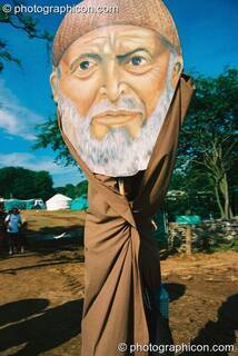 Person in a robe with a very large cardboard head mask at Big Green Gathering 2003. Cheddar, Great Britain. © 2003 Photographicon