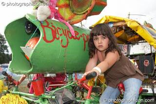 A young girl sitting on the Rinky-Dink mobile pedal-powered sound-system at Big Green Gathering 2006. Burrington, Cheddar, Great Britain. © 2006 Photographicon