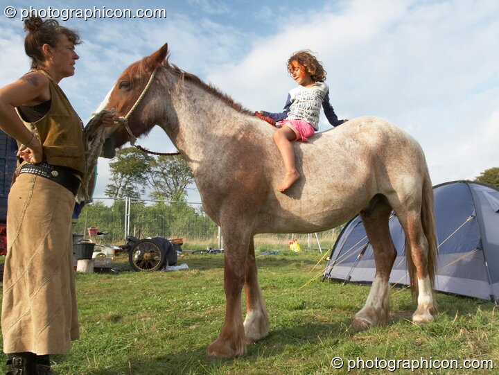 A small girl sitting on horse back in the Horse-drawn Camp at Big Green Gathering 2006. Burrington, Cheddar, Great Britain. © 2006 Photographicon