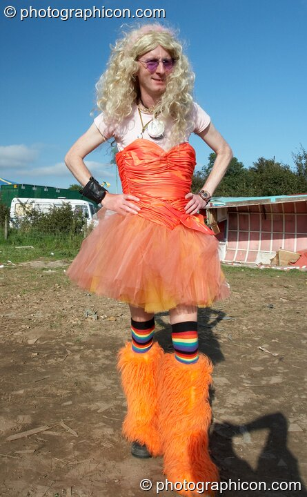 A man wearing a wig, red dress, and orange leggings at Big Green Gathering 2007. Burrington, Cheddar, Great Britain. © 2007 Photographicon