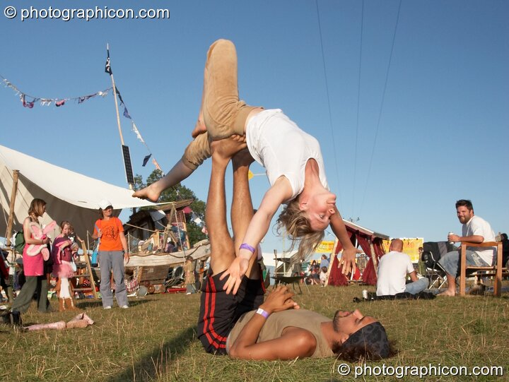 A man lies on his back supporting a woman practicing acrobatics at Big Green Gathering 2007. Burrington, Cheddar, Great Britain. © 2007 Photographicon