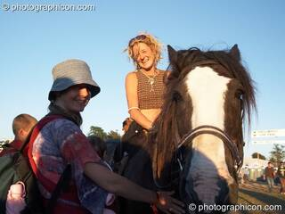 A woman on horseback talks to a friend at Big Green Gathering 2007. Burrington, Cheddar, Great Britain. © 2007 Photographicon