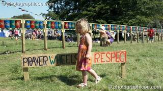 A young girl respects the Tibetan Buddhist prayer wheels in the Healing Field at Big Green Gathering 2007. Burrington, Cheddar, Great Britain. © 2007 Photographicon
