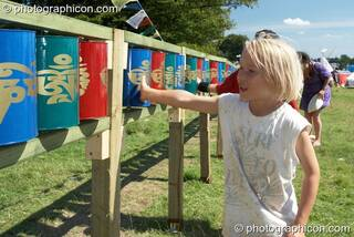 A boy turns the Tibetan Buddhist prayer wheels in the Healing Field at Big Green Gathering 2007. Burrington, Cheddar, Great Britain. © 2007 Photographicon