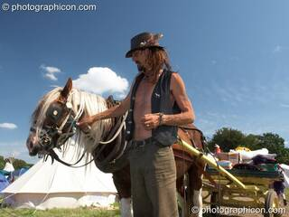 A man holds his horse after a hot day pulling luggage in a cart at Big Green Gathering 2007. Burrington, Cheddar, Great Britain. © 2007 Photographicon