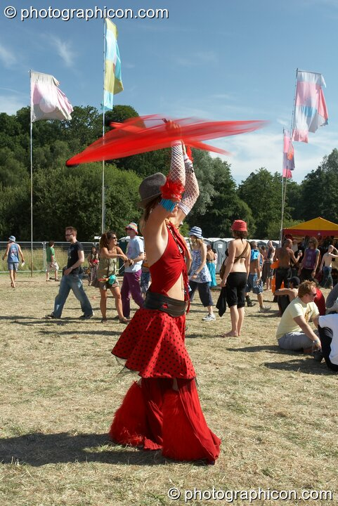 Girl in red twirls red poi above her head at Glade Festival 2005. Aldermaston, Great Britain. © 2005 Photographicon