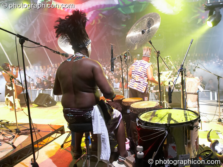 A masked African drummer framed against the illuminated crowd performs with Juno Reactor on the Glade Stage at Glade Festival 2006. Aldermaston, Great Britain. © 2006 Photographicon