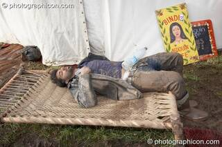 A man caked in mud sleeps uncomfortably on a small seating platform outside the Bedouin Cafe at Glade Festival 2007. Aldermaston, Great Britain. © 2007 Photographicon