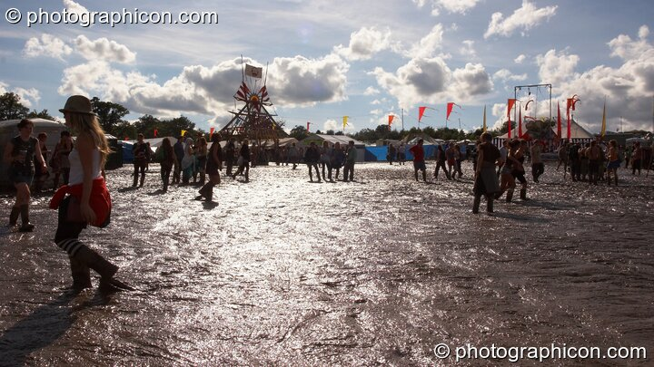 The bright sun reflects off the brown wet muddy expanse silhouetting people walking by at Glade Festival 2007. Aldermaston, Great Britain. © 2007 Photographicon