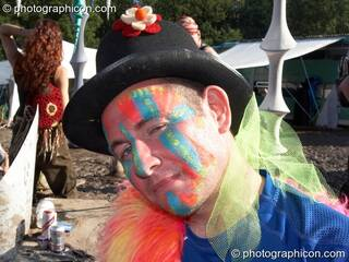 A man wearing a painted face and hat gives a sideways look at Glade Festival 2007. Aldermaston, Great Britain. © 2007 Photographicon