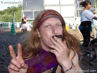A long haired man with a false moustache smokes a cigarette at Glade Festival 2007. Aldermaston, Great Britain. © 2007 Photographicon