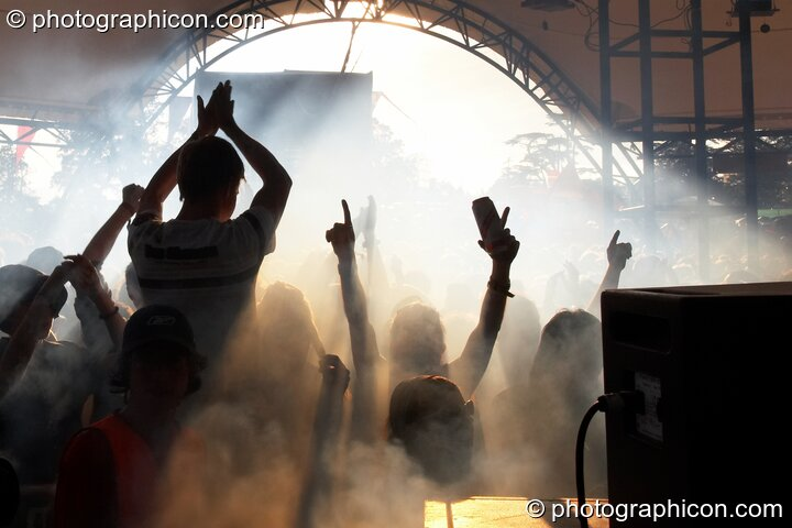 The cheering and waving Glade Stage audience are silhouetted by the Sun and stage smoke at Glade Festival 2007. Aldermaston, Great Britain. © 2007 Photographicon