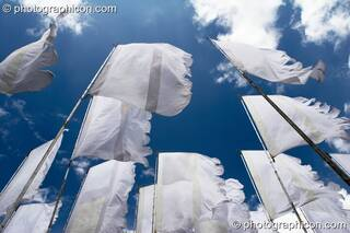 Shot from below, white flags flutter against a deep blue sky and fluffy clouds at Glade Festival 2005. Aldermaston, Great Britain. © 2005 Photographicon