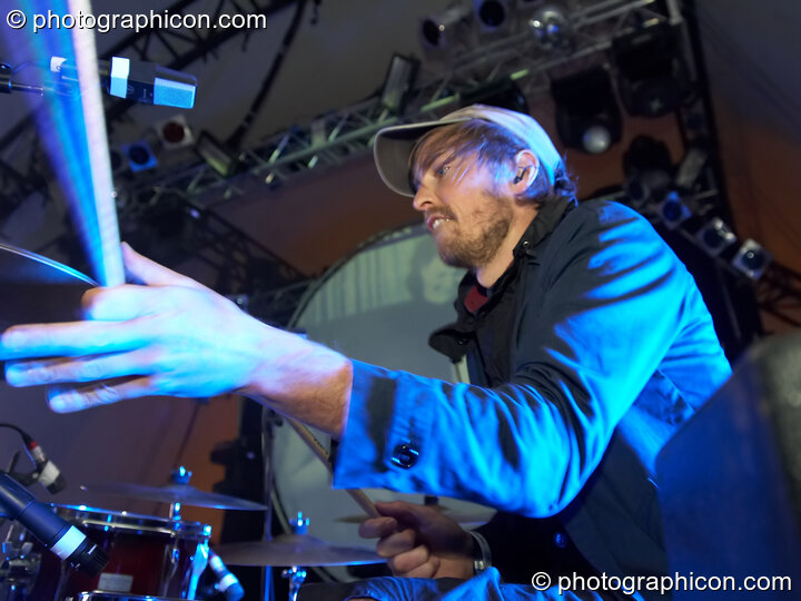 Henrik Vibskov of Trentemoller (Poker Flat Recordings) in close side profile as his stick reaches for the drums on the Glade Stage at Glade Festival 2007. Aldermaston, Great Britain. © 2007 Photographicon