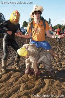 A man wearing a rubber chicken suit dances in the mud with his friend wearing a plastic sheep at Glade Festival 2007. Aldermaston, Great Britain. © 2007 Photographicon