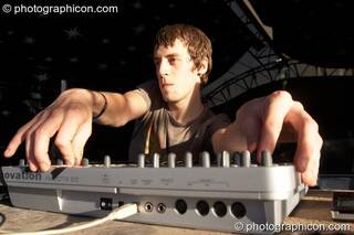 In pre-sunset shadows, the long arms of Matt Allaby (Nano Records) coax big sounds from a midi controller on the Origin Stage at Glade Festival 2007. Aldermaston, Great Britain. © 2007 Photographicon