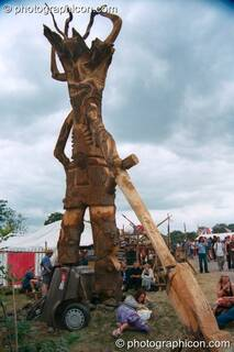Tree Pirates chainsaw sculpture of a tree burying a car at Glastonbury Festival 2002. Pilton, Great Britain. © 2002 Photographicon