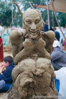 A clay sculpture of a person sitting by the fire at Glastonbury Festival 2002. Pilton, Great Britain. © 2002 Photographicon
