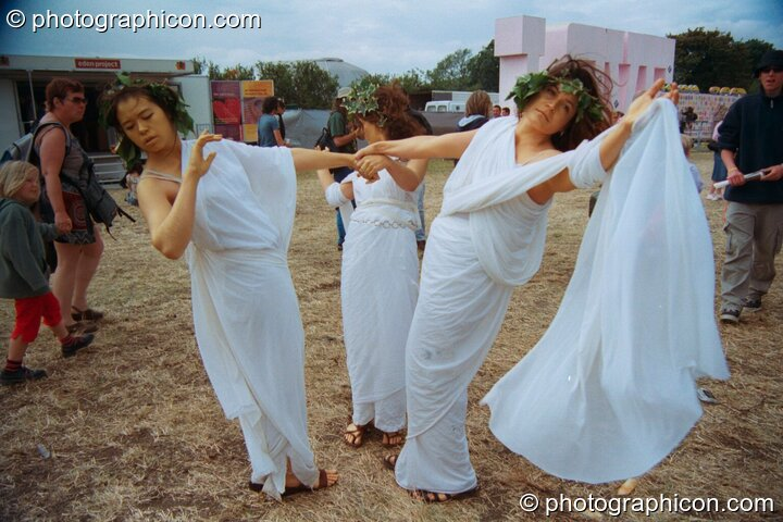 Three women dressed as though in ancient Greece perform a theatrical dance at Glastonbury Festival 2002. Pilton, Great Britain. © 2002 Photographicon