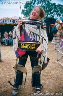 A woman wearing the leg-braces of a Ketamine Simulator in the Lost Vaguess field at Glastonbury Festival 2002. Pilton, Great Britain. © 2002 Photographicon