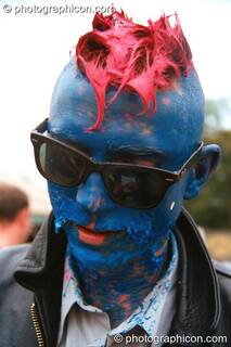 A man with a peeling acrylic painted head in the Lost Vaguess field at Glastonbury Festival 2002. Pilton, Great Britain. © 2002 Photographicon