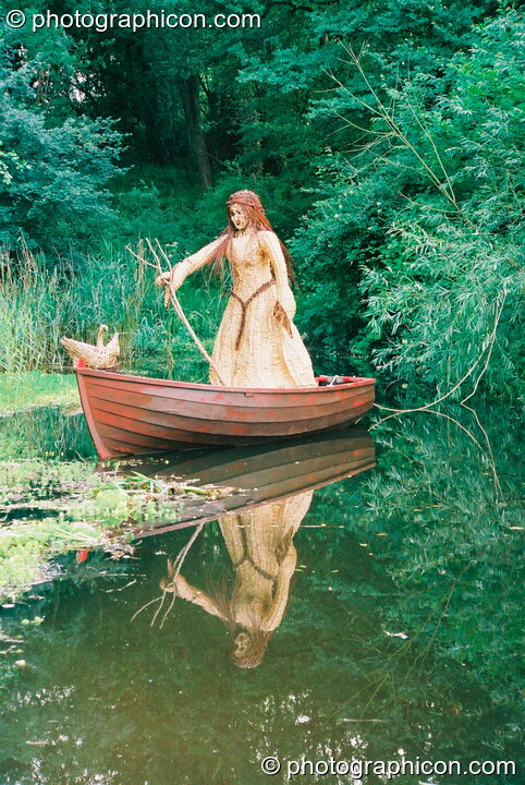 Wicker sculpture of a lady in a boat on a river at Glastonbury Festival 2003. Pilton, Great Britain. © 2003 Photographicon