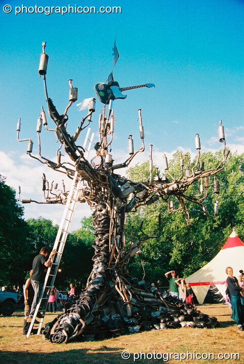 A tree sculpture made from car exhaust pipes in the Lost Vagueness field at Glastonbury Festival 2003. Pilton, Great Britain. © 2003 Photographicon