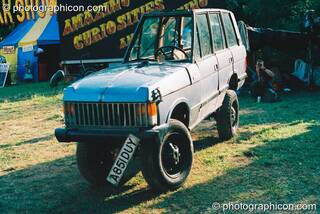 An extra thin Range Rover in the Lost Vagueness field at Glastonbury Festival 2003. Pilton, Great Britain. © 2003 Photographicon