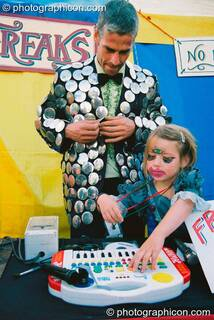 Man and daughter play music for the freak show in the Lost Vagueness field at Glastonbury Festival 2003. Pilton, Great Britain. © 2003 Photographicon