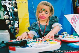 Girl with grotesque make-up plays music for the freak show in the Lost Vagueness field at Glastonbury Festival 2003. Pilton, Great Britain. © 2003 Photographicon