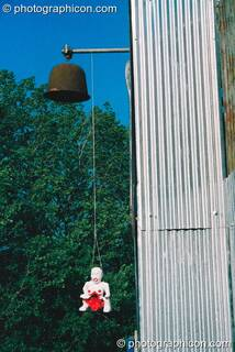 A figurine hanging over the entrance to the chapel in the Lost Vagueness field at Glastonbury Festival 2003. Pilton, Great Britain. © 2003 Photographicon