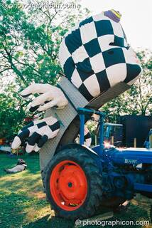 A sculpture of a head attached to a tractor in the Lost Vagueness field at Glastonbury Festival 2003. Pilton, Great Britain. © 2003 Photographicon