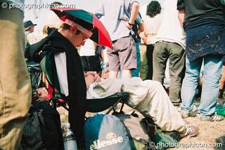 Man with sunhat sleeps through a performance of Yes at Glastonbury Festival 2003. Pilton, Great Britain. © 2003 Photographicon