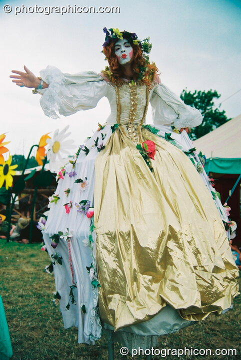 Woman on stilts in a big dress at Glastonbury Festival 2003. Pilton, Great Britain. © 2003 Photographicon