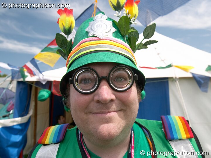Green Policeman with thick glasses and flowers on his helmet at Glastonbury Festival 2005. Pilton, Great Britain. © 2005 Photographicon