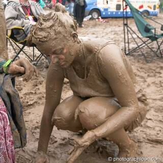Woman wearing a T-shirt is covered head to foot in mud at Glastonbury Festival 2005. Pilton, Great Britain. © 2005 Photographicon