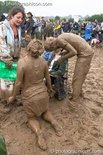 A couple of mud lovers playing at Glastonbury Festival 2005. Pilton, Great Britain. © 2005 Photographicon