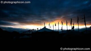 The dawn sun seeps through a crack in ominous black clouds, silhouetting tent and flags at Glastonbury Festival 2005. Pilton, Great Britain. © 2005 Photographicon