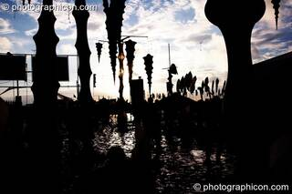 The sun reflects off the mud, silhouetting hanging decor in the ID Spiral arena of the Dance Village at Glastonbury Festival 2007. Pilton, United Kingdom. © 2007 Photographicon