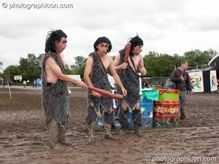The men dressed as cavemen wander through the mud at Glastonbury Festival 2007. Pilton, United Kingdom. © 2007 Photographicon